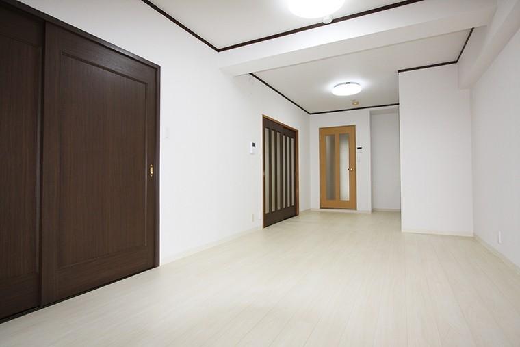 白色の床に木目調の建具が映えるLDK。